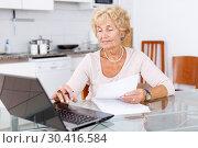 Senior woman filling up documents. Стоковое фото, фотограф Яков Филимонов / Фотобанк Лори