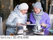 Купить «Senior females reading city map in outdoors cafe», фото № 30416648, снято 26 ноября 2017 г. (c) Яков Филимонов / Фотобанк Лори