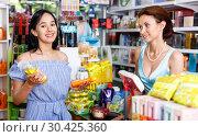 Купить «Smiling saleswoman helping to girl client with purchases in salon», фото № 30425360, снято 21 июня 2018 г. (c) Яков Филимонов / Фотобанк Лори
