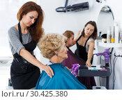 Купить «Hairdresser seating female client in chair», фото № 30425380, снято 26 июня 2018 г. (c) Яков Филимонов / Фотобанк Лори