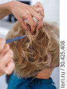 Купить «Hands of hairdresser making hairstyle for female», фото № 30425408, снято 26 июня 2018 г. (c) Яков Филимонов / Фотобанк Лори