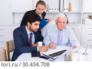 Купить «Employees are demonstrating reports on laptop to mature boss», фото № 30434708, снято 27 июня 2017 г. (c) Яков Филимонов / Фотобанк Лори
