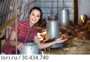 Купить «woman farmer holding bucket with chicken forage in hen house», фото № 30434740, снято 23 апреля 2019 г. (c) Яков Филимонов / Фотобанк Лори