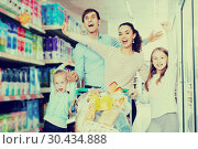Купить «Family with two daughters shopping in local supermarket», фото № 30434888, снято 25 мая 2019 г. (c) Яков Филимонов / Фотобанк Лори