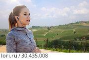 Купить «sportswoman in earphones running outdoors», фото № 30435008, снято 17 октября 2015 г. (c) Syda Productions / Фотобанк Лори
