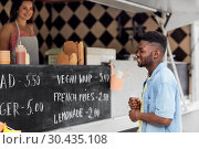 Купить «male customer looking at menu board at food truck», фото № 30435108, снято 1 августа 2017 г. (c) Syda Productions / Фотобанк Лори