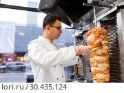 Купить «chef slicing doner meat from spit at kebab shop», фото № 30435124, снято 7 декабря 2017 г. (c) Syda Productions / Фотобанк Лори