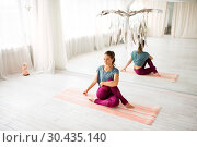 Купить «woman doing yoga exercise at studio», фото № 30435140, снято 21 июня 2018 г. (c) Syda Productions / Фотобанк Лори