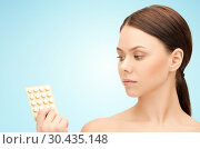 young woman with pills over blue background. Стоковое фото, фотограф Syda Productions / Фотобанк Лори