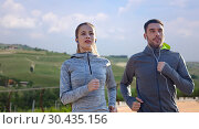 Купить «happy couple with earphones running outdoors», фото № 30435156, снято 17 октября 2015 г. (c) Syda Productions / Фотобанк Лори