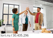 Купить «happy creative team making high five at office», фото № 30435296, снято 11 марта 2018 г. (c) Syda Productions / Фотобанк Лори