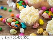 Купить «cupcake with chocolate eggs and candies on table», фото № 30435552, снято 15 марта 2018 г. (c) Syda Productions / Фотобанк Лори