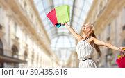 Купить «happy woman with shopping bags over mall», фото № 30435616, снято 19 июня 2013 г. (c) Syda Productions / Фотобанк Лори