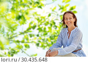 Купить «happy smiling woman over green natural background», фото № 30435648, снято 15 июня 2018 г. (c) Syda Productions / Фотобанк Лори