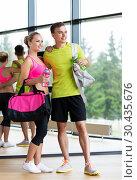 Купить «sportive couple with water bottles and bags in gym», фото № 30435676, снято 29 июня 2014 г. (c) Syda Productions / Фотобанк Лори