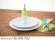 Купить «easter egg in cup holder, plates and cutlery», фото № 30435732, снято 15 марта 2018 г. (c) Syda Productions / Фотобанк Лори