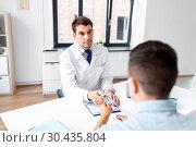 Купить «doctor giving medicine to male patient at hospital», фото № 30435804, снято 25 августа 2018 г. (c) Syda Productions / Фотобанк Лори