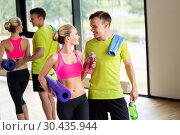 Купить «couple with bottles, exercise mat and towel in gym», фото № 30435944, снято 29 июня 2014 г. (c) Syda Productions / Фотобанк Лори