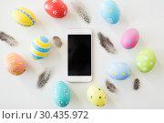 Купить «smartphone with easter eggs and quail feathers», фото № 30435972, снято 15 марта 2018 г. (c) Syda Productions / Фотобанк Лори