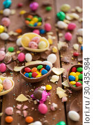 Купить «chocolate eggs and candy drops on wooden table», фото № 30435984, снято 15 марта 2018 г. (c) Syda Productions / Фотобанк Лори