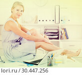 young female in dress sitting on table in workplace in office. Стоковое фото, фотограф Яков Филимонов / Фотобанк Лори