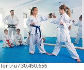 Купить «Pair of little girls practicing new karate moves during class», фото № 30450656, снято 25 марта 2017 г. (c) Яков Филимонов / Фотобанк Лори