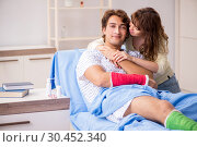 Купить «Loving wife looking after injured husband in hospital», фото № 30452340, снято 24 сентября 2018 г. (c) Elnur / Фотобанк Лори