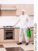 Купить «Professional contractor doing pest control at kitchen», фото № 30453620, снято 29 октября 2018 г. (c) Elnur / Фотобанк Лори