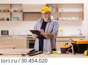 Купить «Aged contractor repairman working in the kitchen», фото № 30454020, снято 20 декабря 2018 г. (c) Elnur / Фотобанк Лори