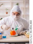 Купить «Scientist working in lab on GMO fruits and vegetables», фото № 30454360, снято 5 декабря 2018 г. (c) Elnur / Фотобанк Лори