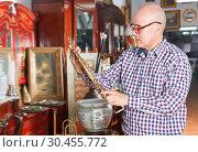Купить «Adult man carefully examining antiques», фото № 30455772, снято 15 мая 2018 г. (c) Яков Филимонов / Фотобанк Лори