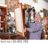 Купить «Ordinary male carefully examining antiques», фото № 30455788, снято 15 мая 2018 г. (c) Яков Филимонов / Фотобанк Лори