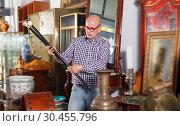Купить «Mature male carefully examining antiques», фото № 30455796, снято 15 мая 2018 г. (c) Яков Филимонов / Фотобанк Лори