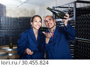 man and women coworkers looking at bubbly wine in bottle standing in wine cellar. Стоковое фото, фотограф Яков Филимонов / Фотобанк Лори
