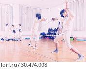 Купить «Serious group practicing fencing techniques», фото № 30474008, снято 30 мая 2018 г. (c) Яков Филимонов / Фотобанк Лори