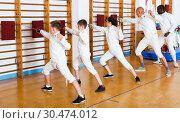 Купить «Group practicing fencing techniques in gym», фото № 30474012, снято 30 мая 2018 г. (c) Яков Филимонов / Фотобанк Лори