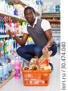 Купить «Active African man holding list of goods», фото № 30474040, снято 7 ноября 2018 г. (c) Яков Филимонов / Фотобанк Лори