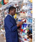 Купить «seller organizing assortment of items on shelves and racks», фото № 30474252, снято 21 января 2019 г. (c) Яков Филимонов / Фотобанк Лори