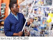Купить «seller organizing assortment of items on shelves and racks», фото № 30474260, снято 21 января 2019 г. (c) Яков Филимонов / Фотобанк Лори