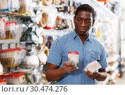 Купить «seller organizing assortment of items on shelves and racks», фото № 30474276, снято 21 января 2019 г. (c) Яков Филимонов / Фотобанк Лори