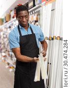 Купить «seller organizing assortment of items on shelves and racks», фото № 30474284, снято 21 января 2019 г. (c) Яков Филимонов / Фотобанк Лори