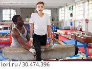 Купить «Male coach training teenage boy on gymnastic equipment at acrobatic hall», фото № 30474396, снято 17 января 2019 г. (c) Яков Филимонов / Фотобанк Лори