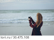 Купить «Woman using mobile phone at beach», фото № 30475108, снято 14 ноября 2018 г. (c) Wavebreak Media / Фотобанк Лори