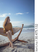 Купить «Young woman sitting on hammock at beach », фото № 30475132, снято 14 ноября 2018 г. (c) Wavebreak Media / Фотобанк Лори