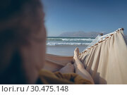 Купить «Woman relaxing on hammock while lying at beach », фото № 30475148, снято 14 ноября 2018 г. (c) Wavebreak Media / Фотобанк Лори