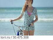 Купить «Happy woman holding bicycle at beach on a sunny day», фото № 30475308, снято 14 ноября 2018 г. (c) Wavebreak Media / Фотобанк Лори