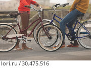 Купить «Couple standing while holding bicycle at promenade», фото № 30475516, снято 14 ноября 2018 г. (c) Wavebreak Media / Фотобанк Лори