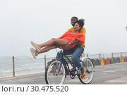 Купить «Couple enjoying at bicycle while riding at pavement», фото № 30475520, снято 14 ноября 2018 г. (c) Wavebreak Media / Фотобанк Лори