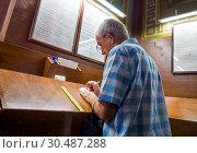 Купить «Мужчина в храме пишет церковную записку», фото № 30487288, снято 22 августа 2018 г. (c) Вячеслав Палес / Фотобанк Лори