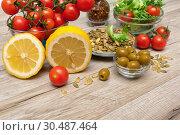 Купить «Different foods on a wooden background», фото № 30487464, снято 21 октября 2013 г. (c) Ласточкин Евгений / Фотобанк Лори